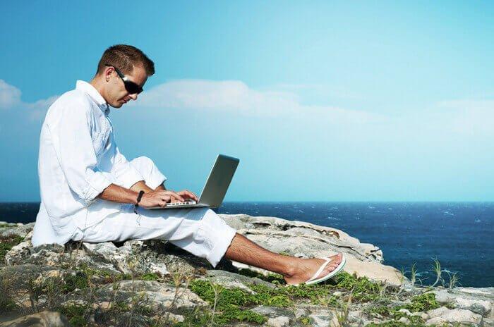 человек с ноутбуком на природе